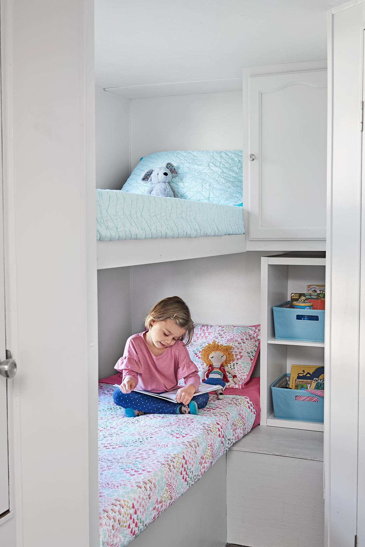 young girl reading in camper bedroom bunk bed