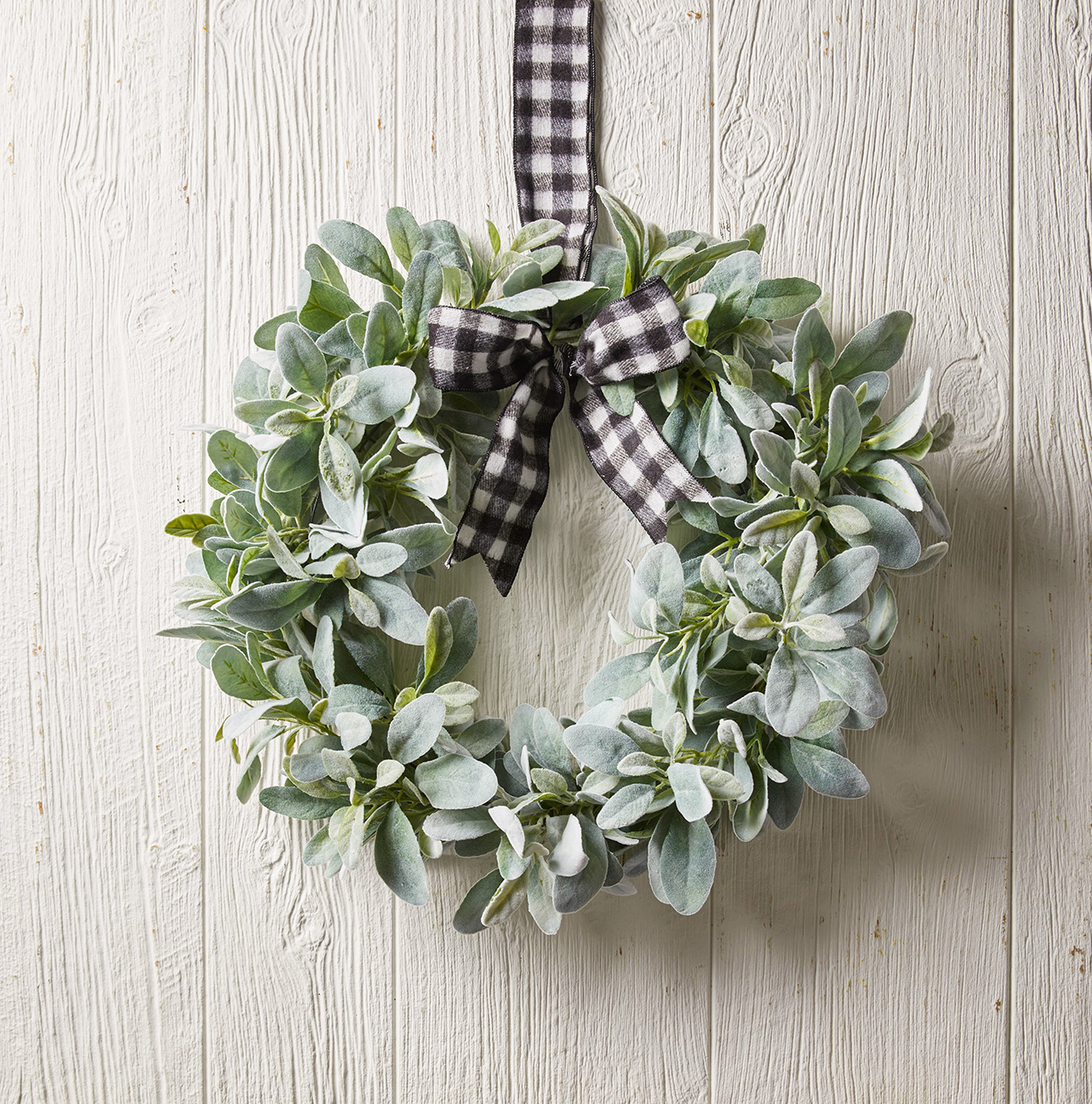 wreath with pale green leaves and plaid ribbon