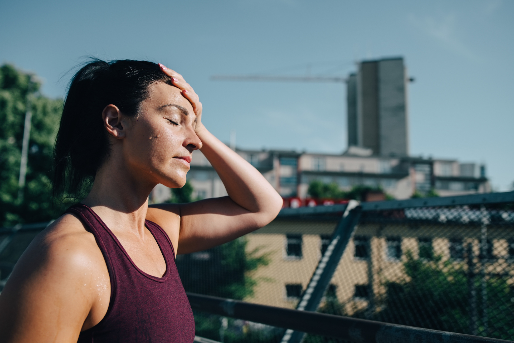 Exhausted sportswoman wiping sweat on forehead during sunny day