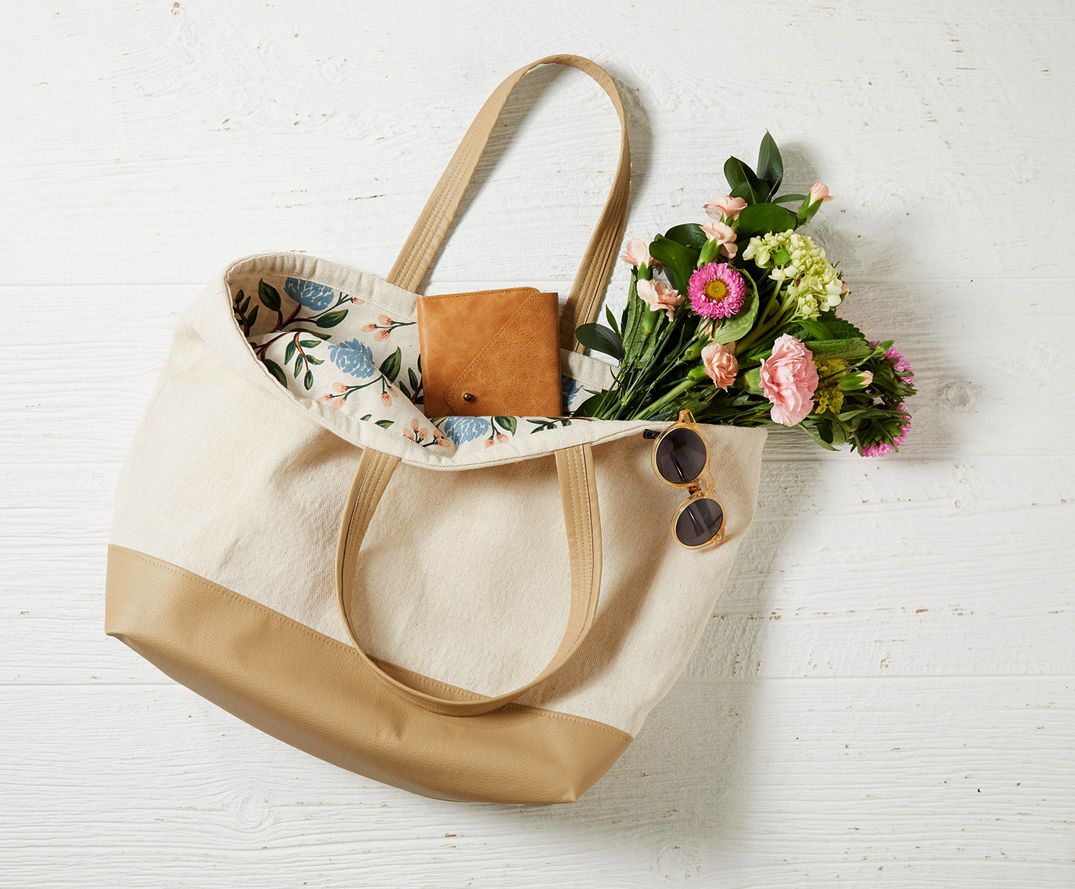 flowers, sunglasses and wallet in beige tote bag