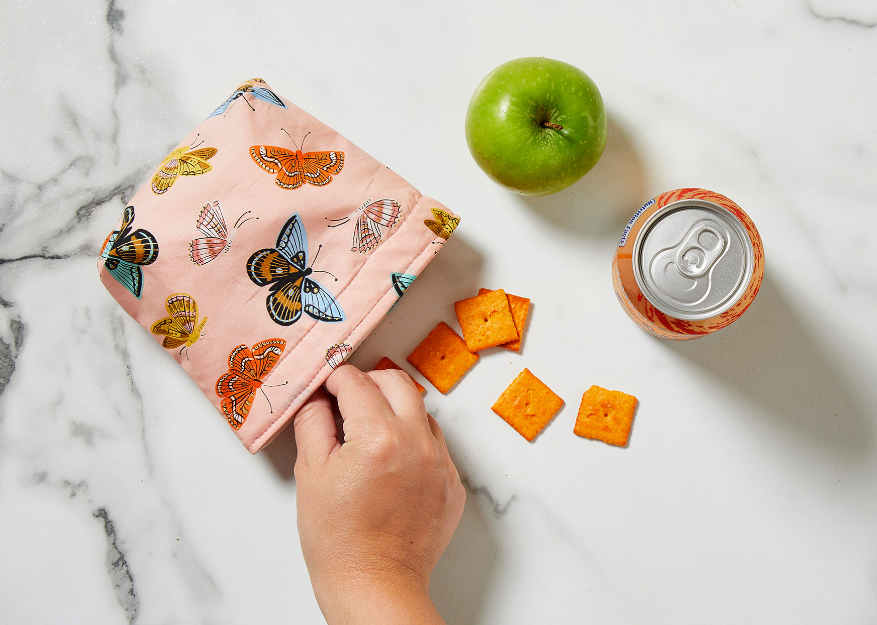 hand grabbing cracker from butterfly patterned snack pouch
