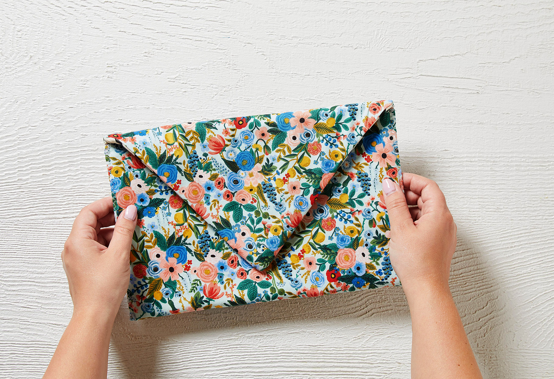 two hands holding flowered envelope clutch