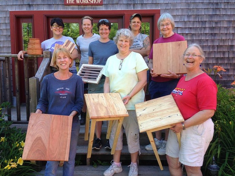 Group of women standing outside holding wood tables