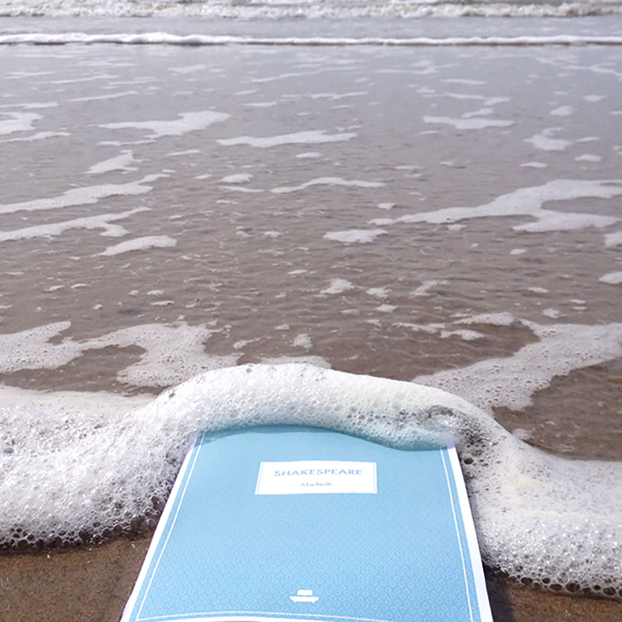 A blue book on the beach, with water coming up over the book