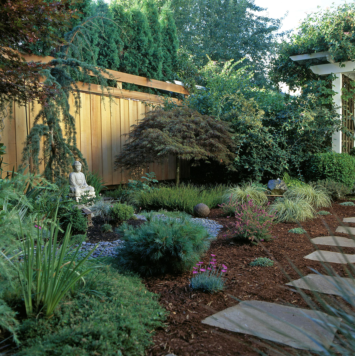 landscaped yard with ornamental grasses, buddha, and wooden fence