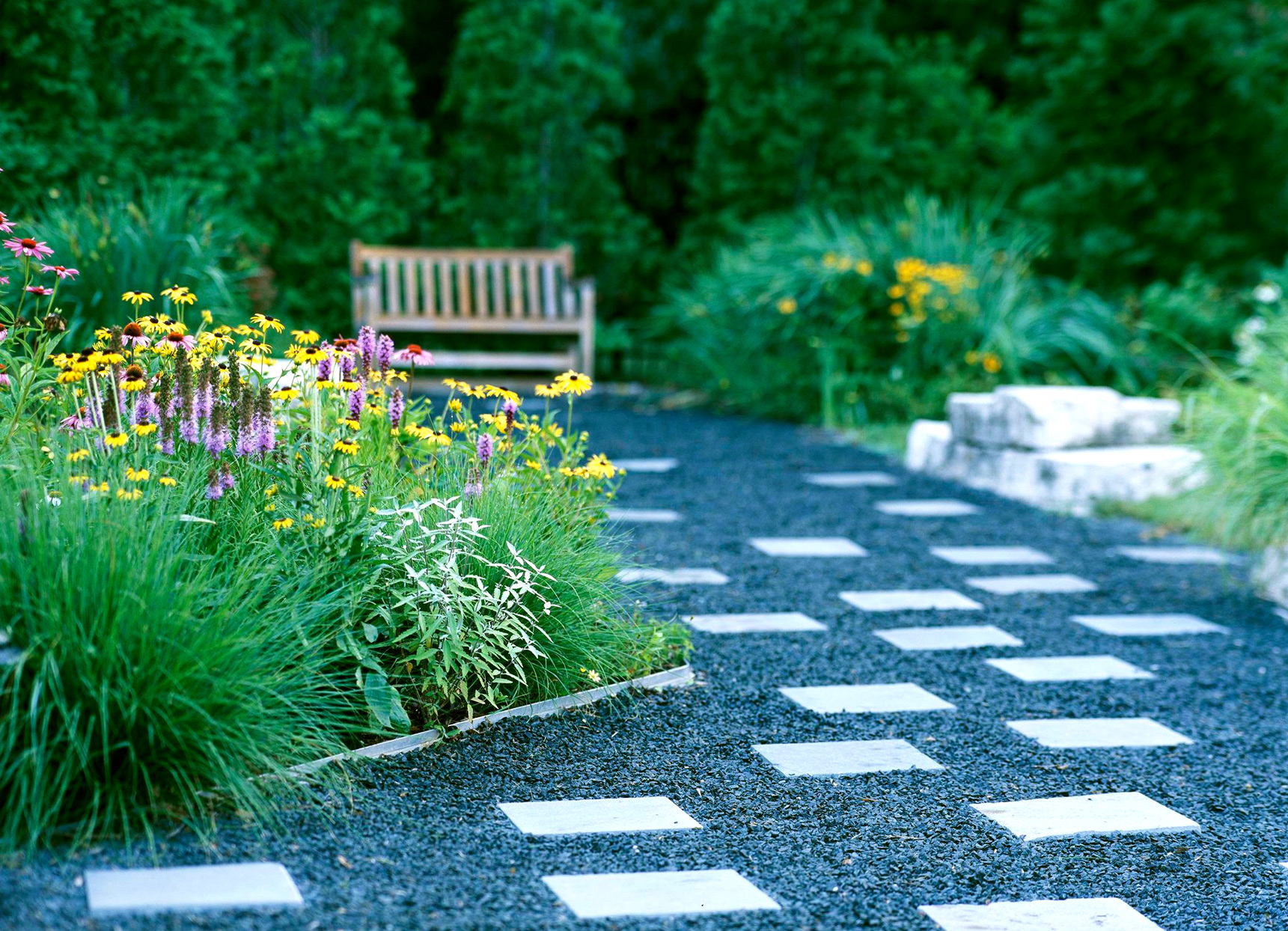 pebbled path with checkered blocks and wild flowers