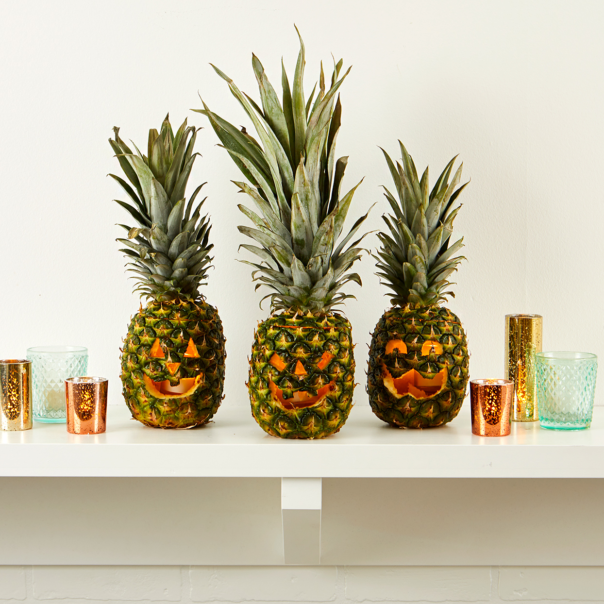 pineapple jack o lanterns on white shelf