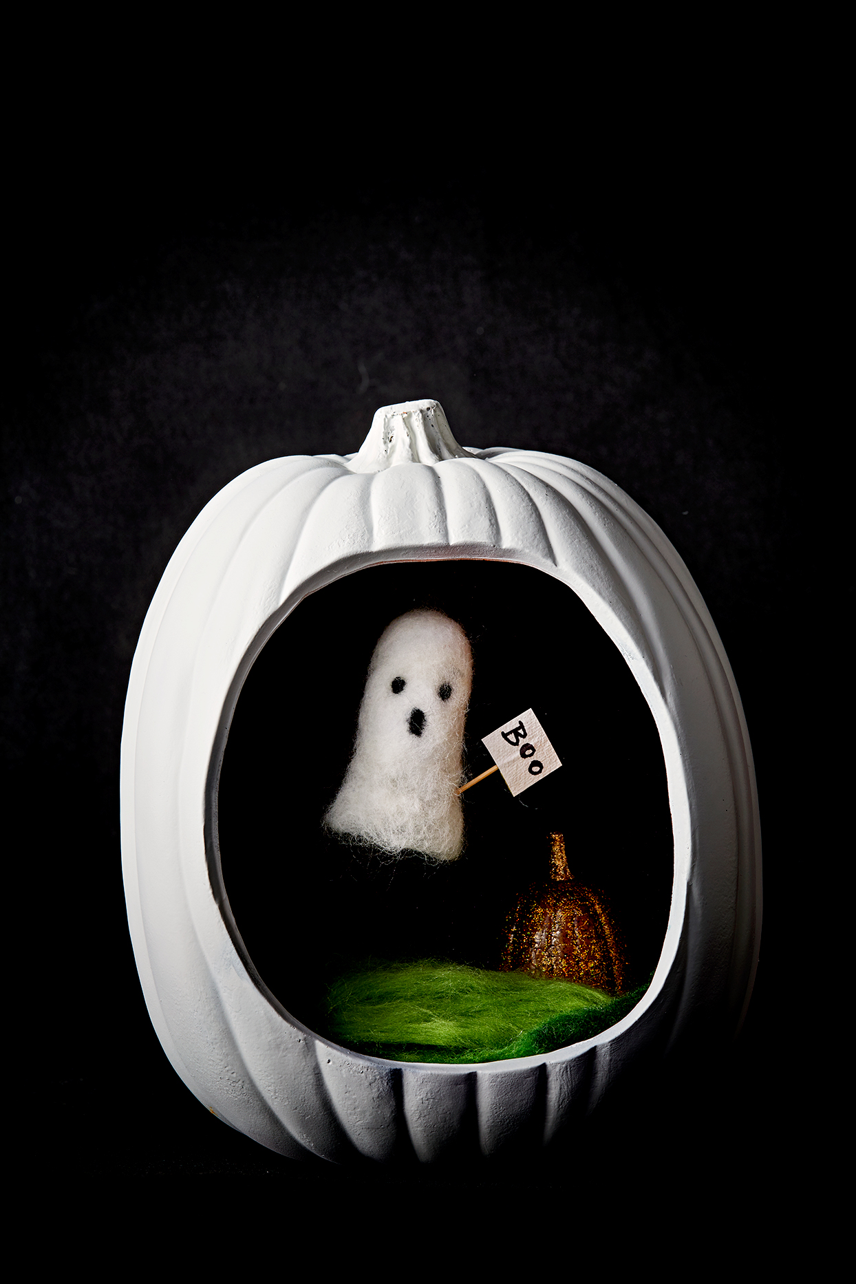 Ghost inside white pumpkin holding boo sign
