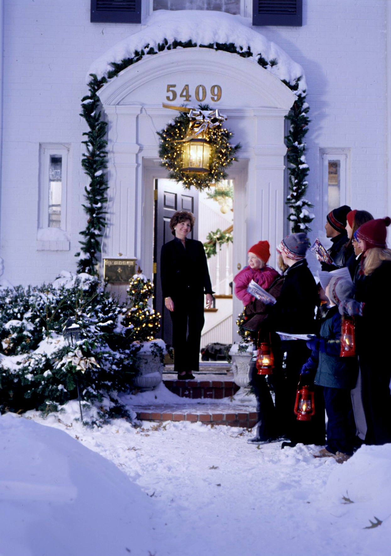 Carolers singing to person in front door
