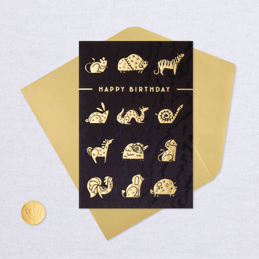 """Black card with gold animals and the words """"happy birthday"""" on the front"""