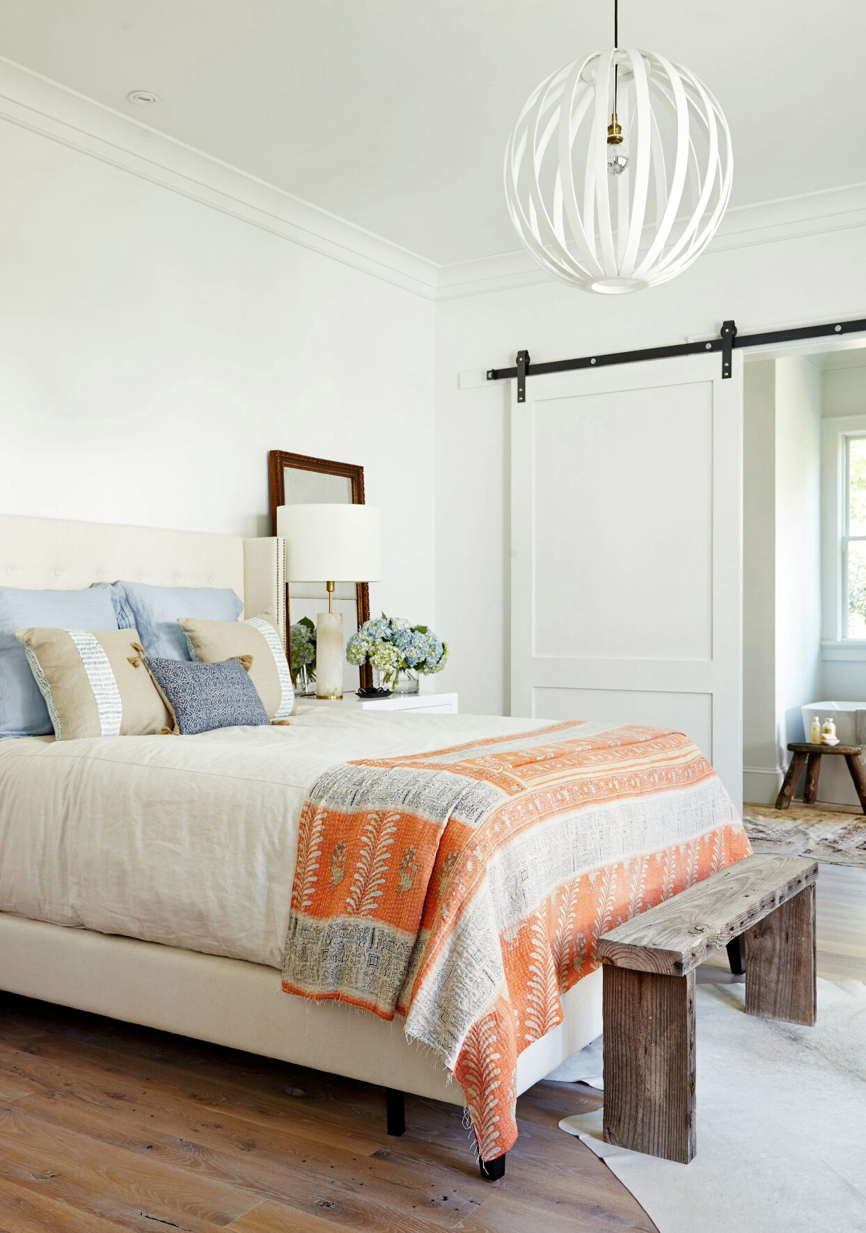blue and orange accents on white bed
