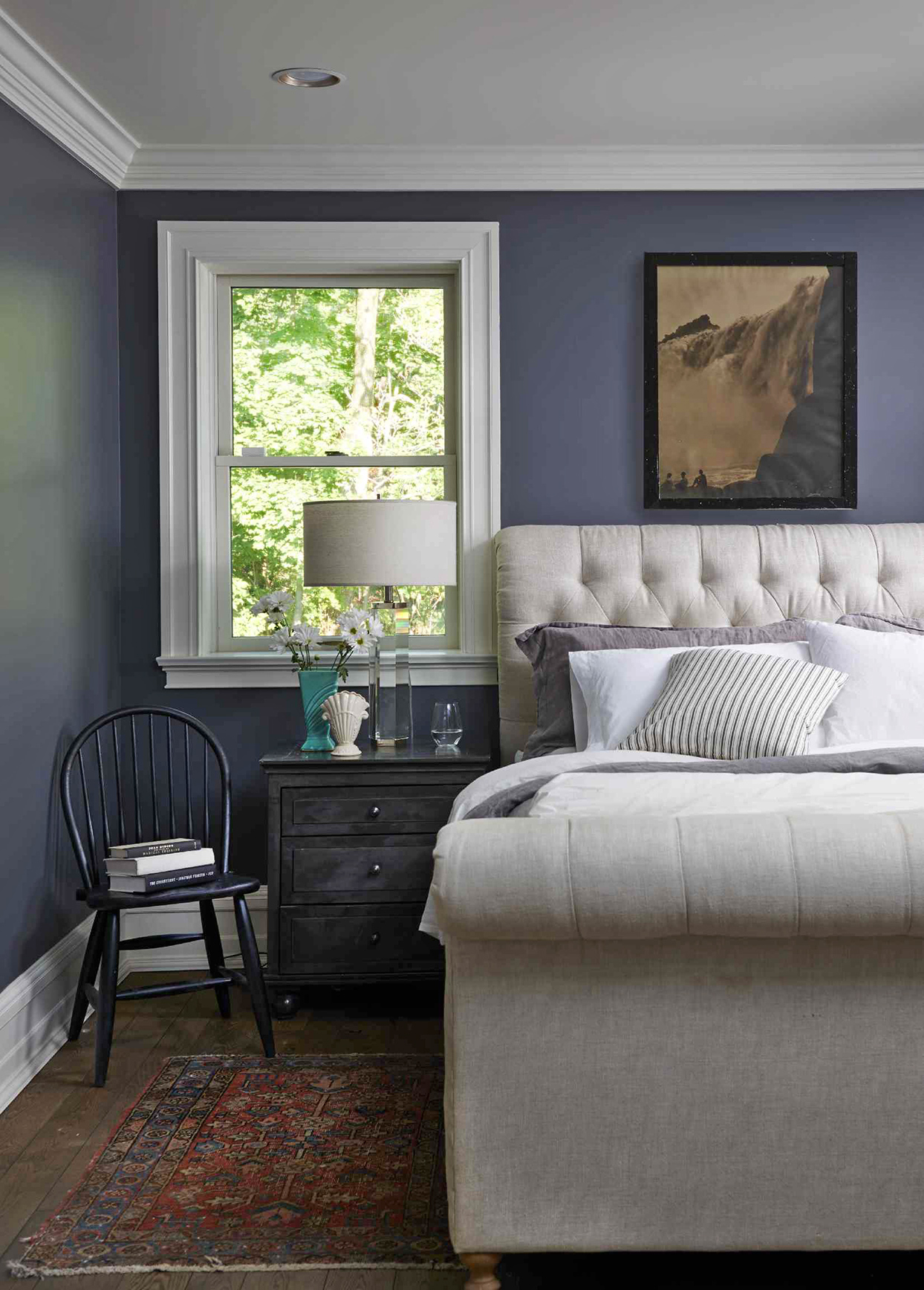 navy bedroom with painting and window