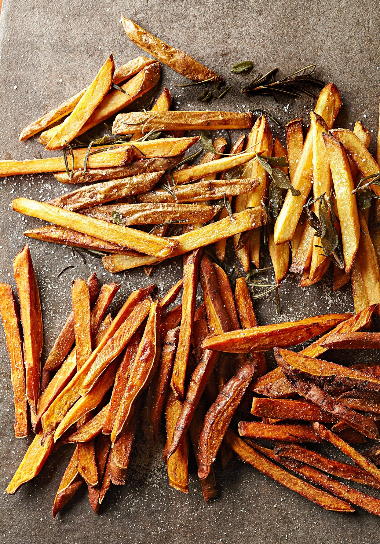 Homemade fries regular and sweet potato with herbs on dark surface