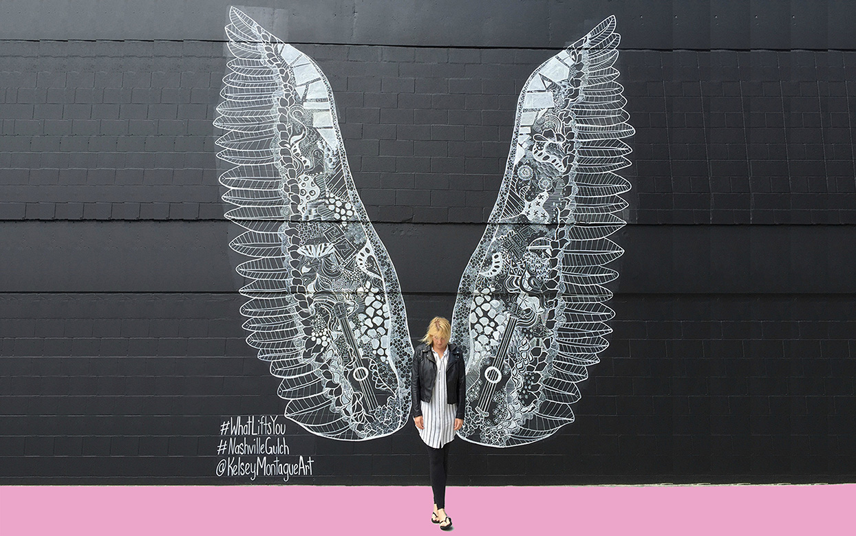 nashville mural of white wings with woman standing in the middle