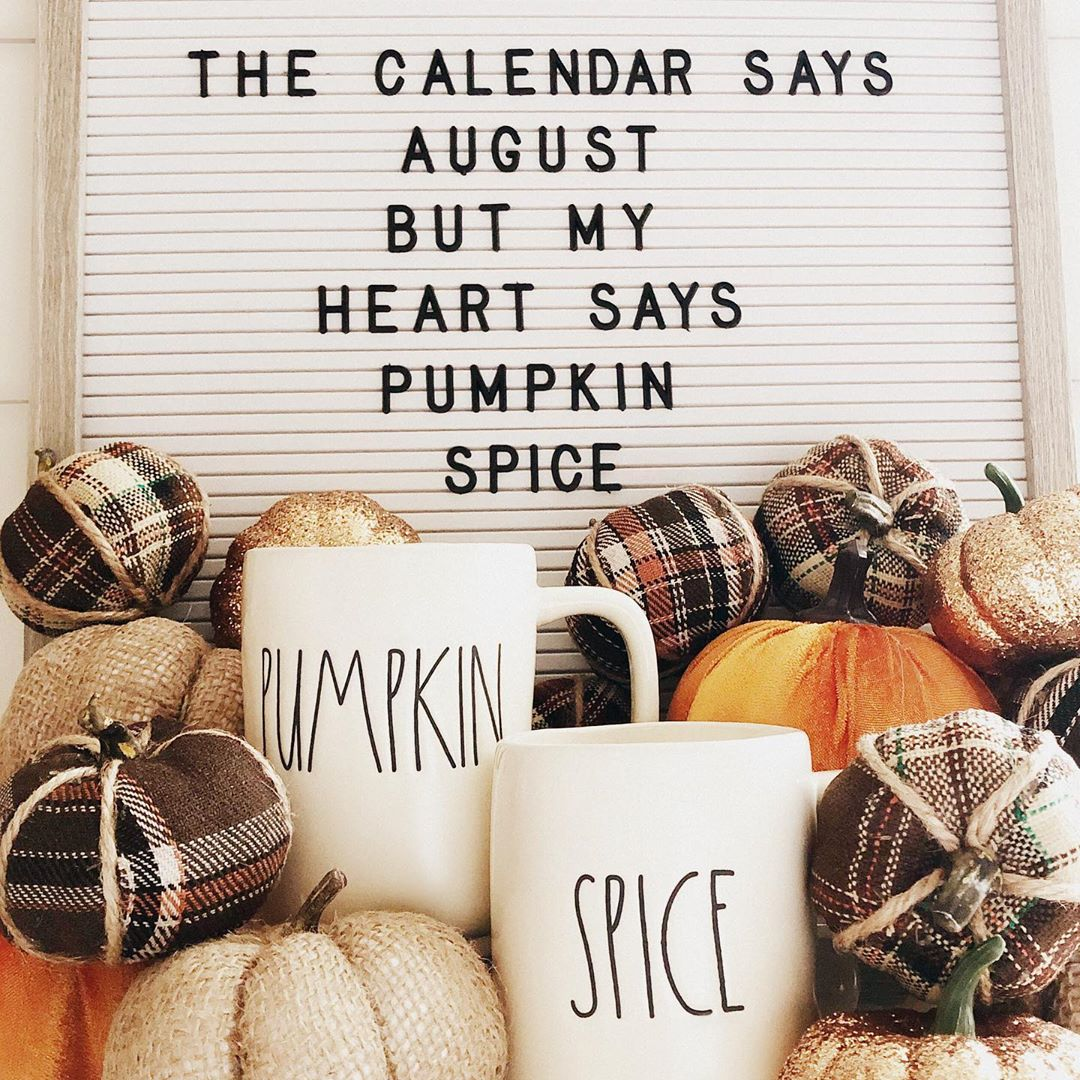 "Two white Rae Dunn mugs next to a pile of fabric pumpkins, under a sign that says ""the calendar says august but my heart says pumpkin spice"""