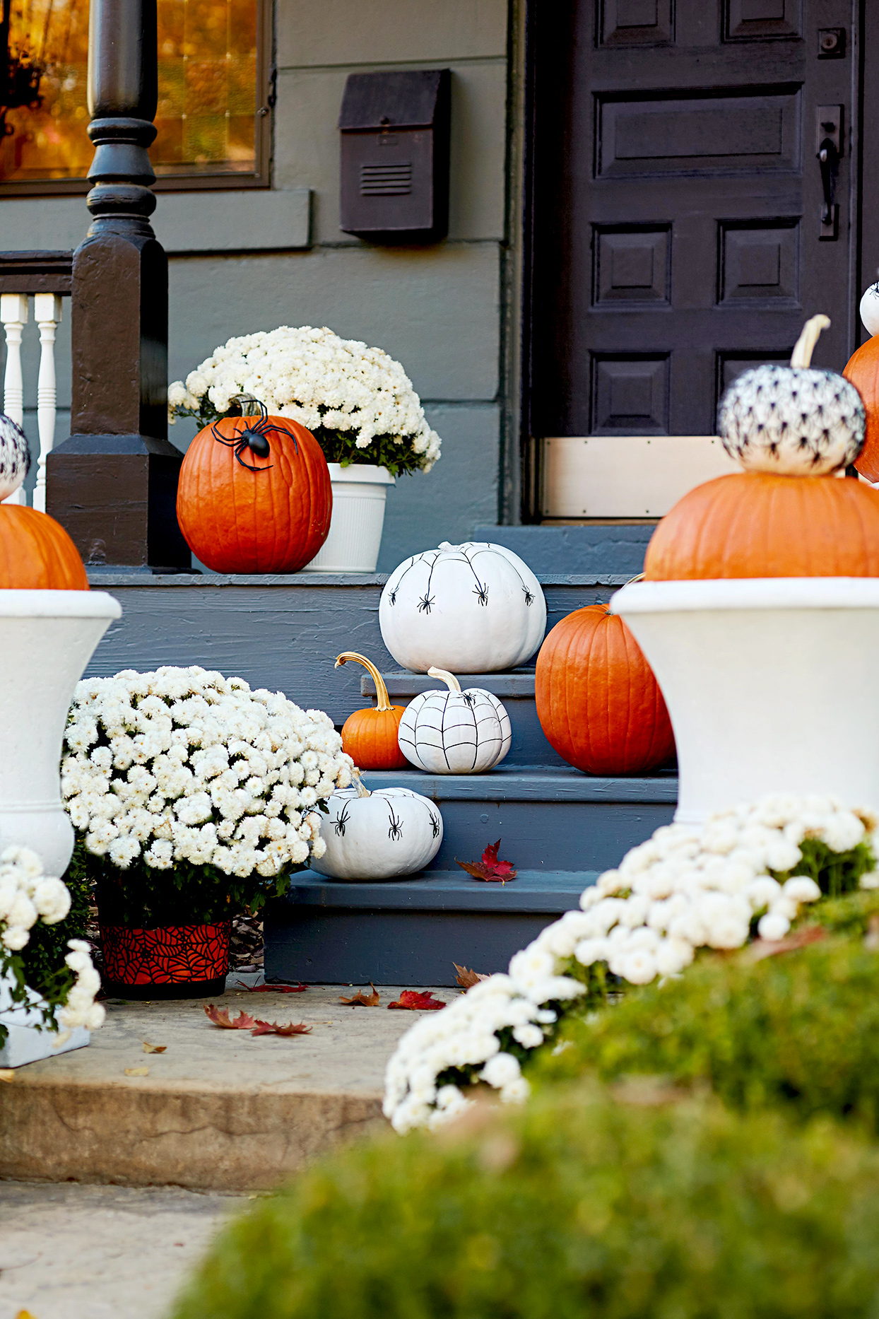 Front porch with pumpkins, white flowers