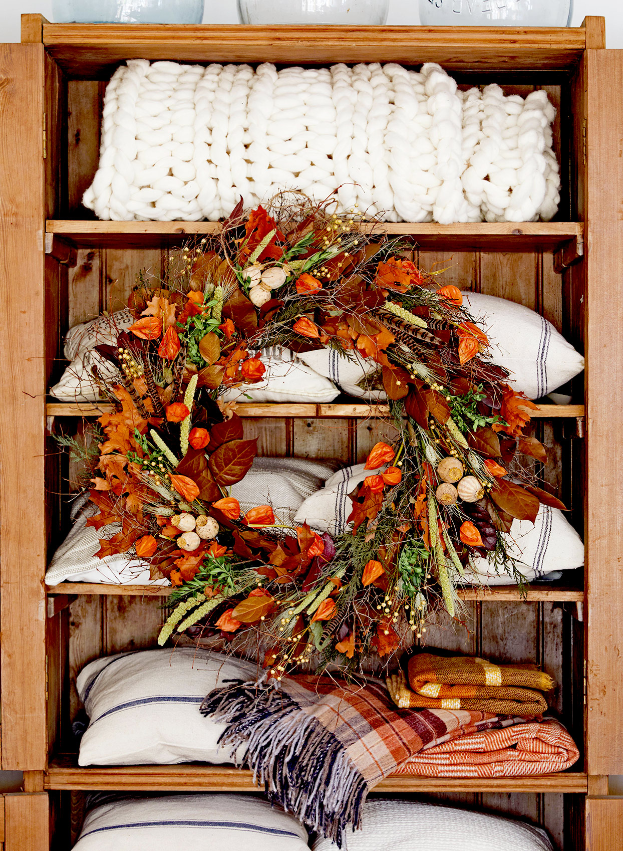 Wooden shelving with pillows, wreath