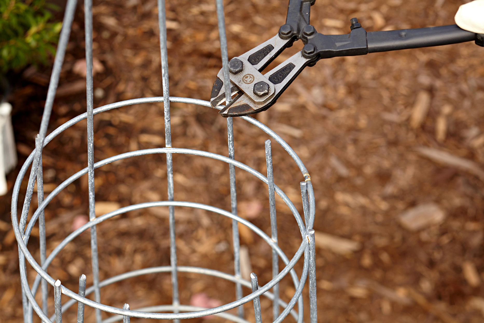 using wire cutters to trim gabion cage
