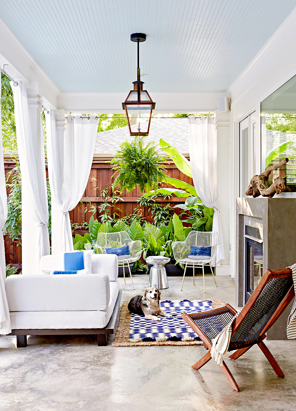 Porch with couch, curtains, dog