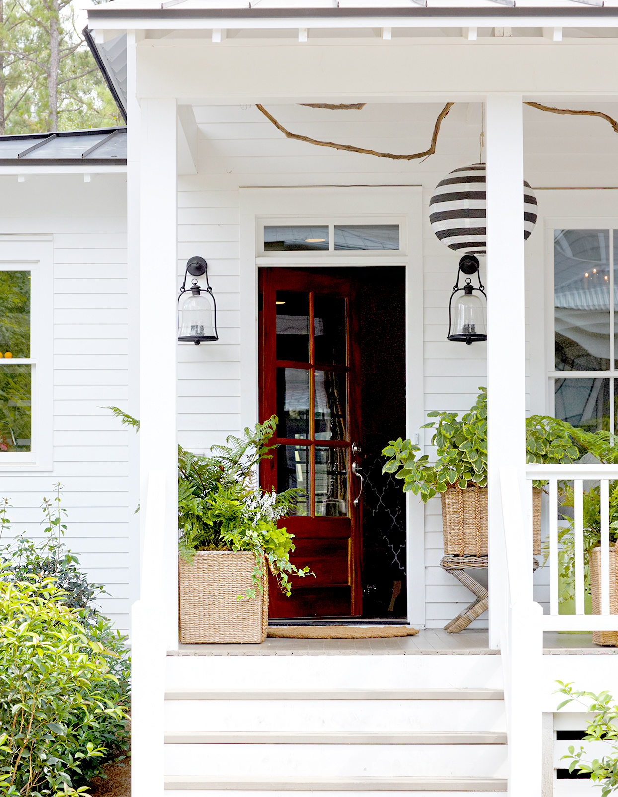 Front porch with plants, black door