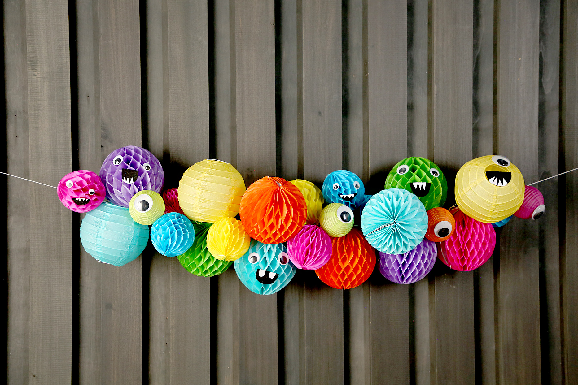Colorful paper lantern monster garland on wood wall