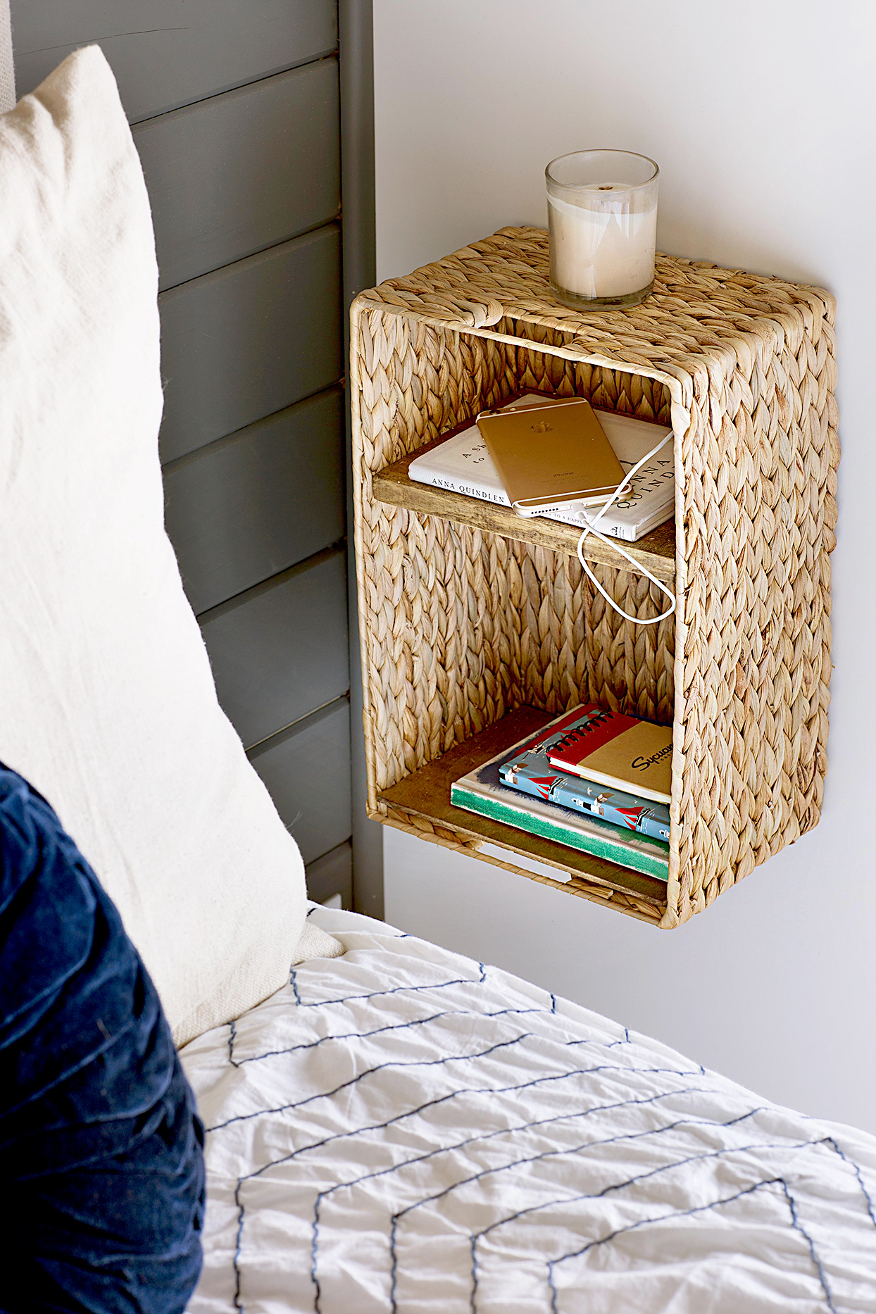 Hanging wicker shelf holding books and laptop