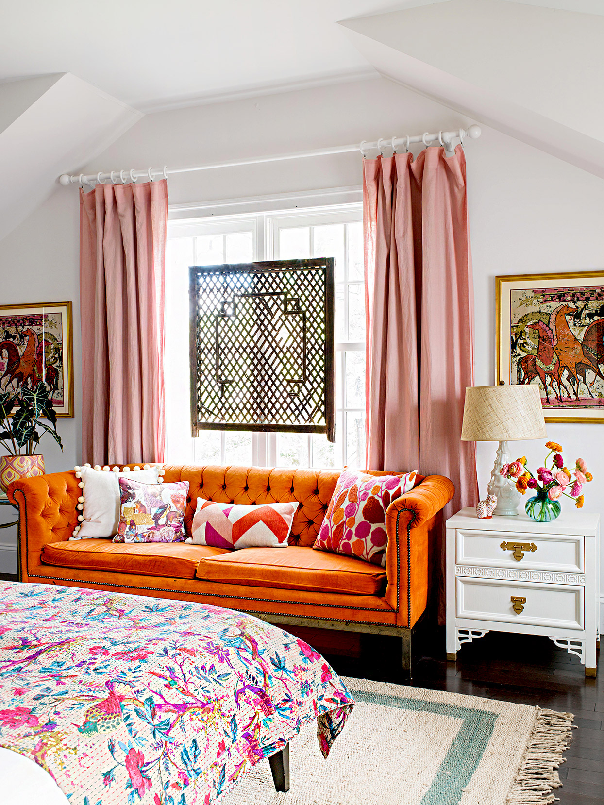 Bedroom with orange couch and colorful bedspread