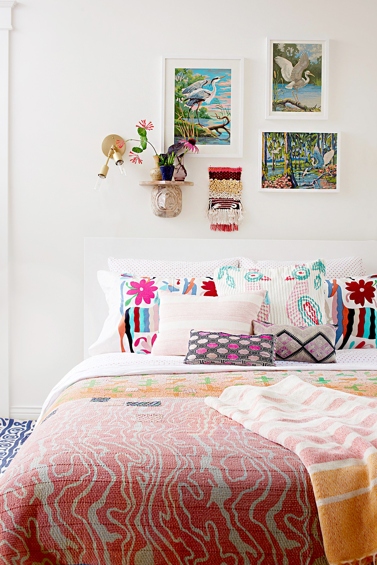 Bed with colorful pillows and wall artwork