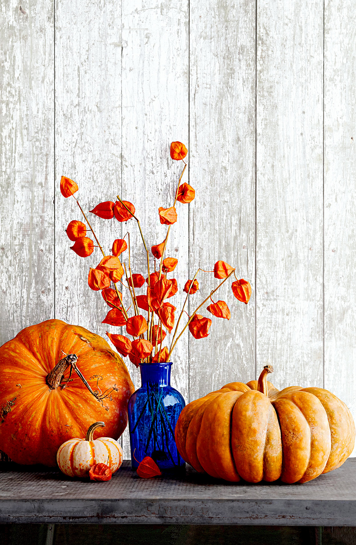 Fall décor in blue glass vase with pumpkins