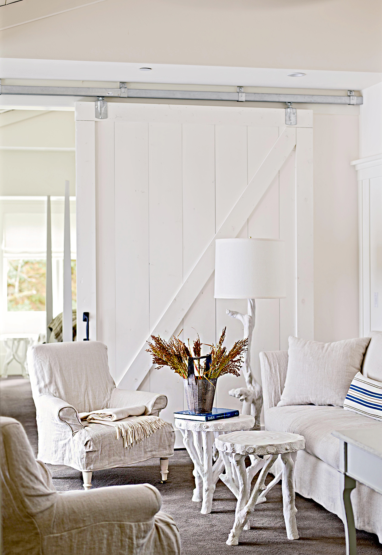 Seating area with white furniture and sliding barn door
