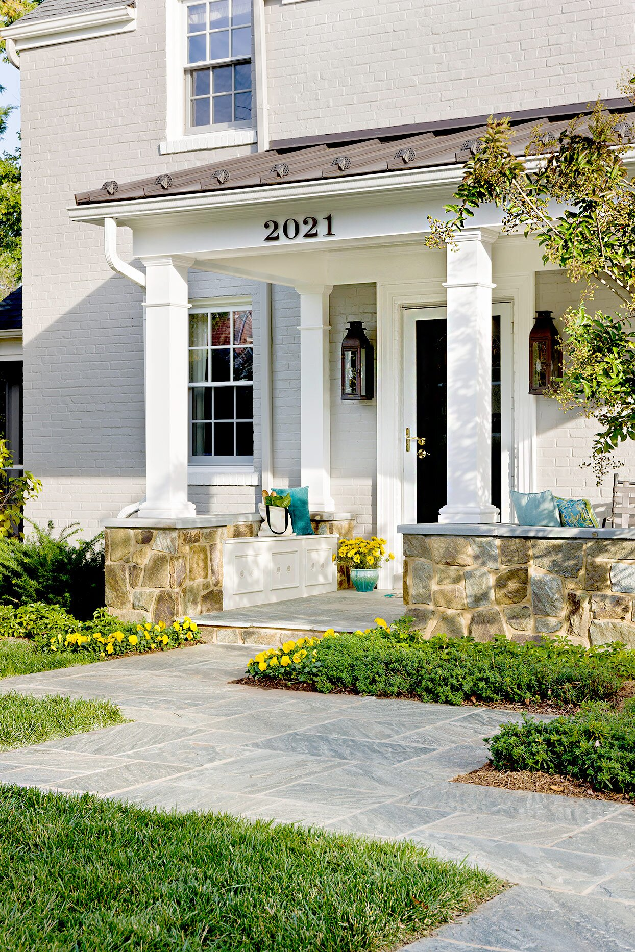 Front entryway with pillars and stone walkway