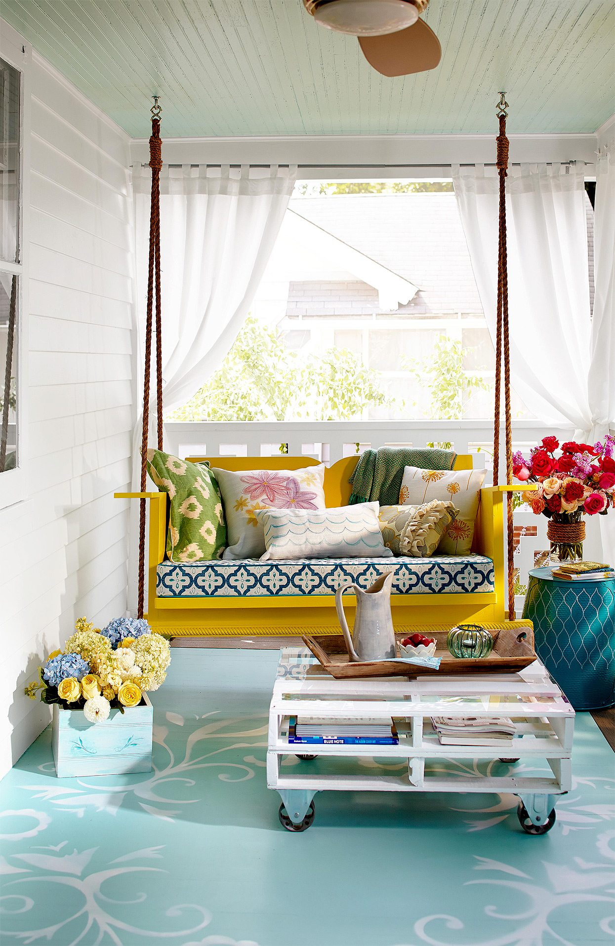 bold front porch with curtains and yellow swing
