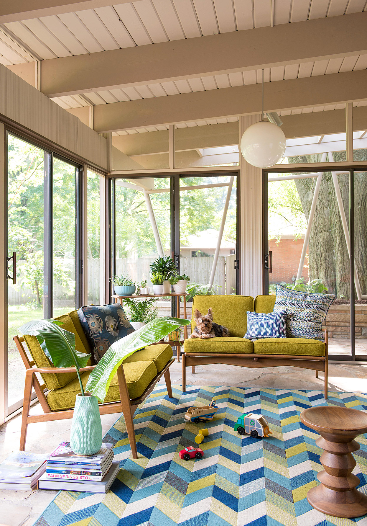 midcentury porch with green loveseats and geo rug
