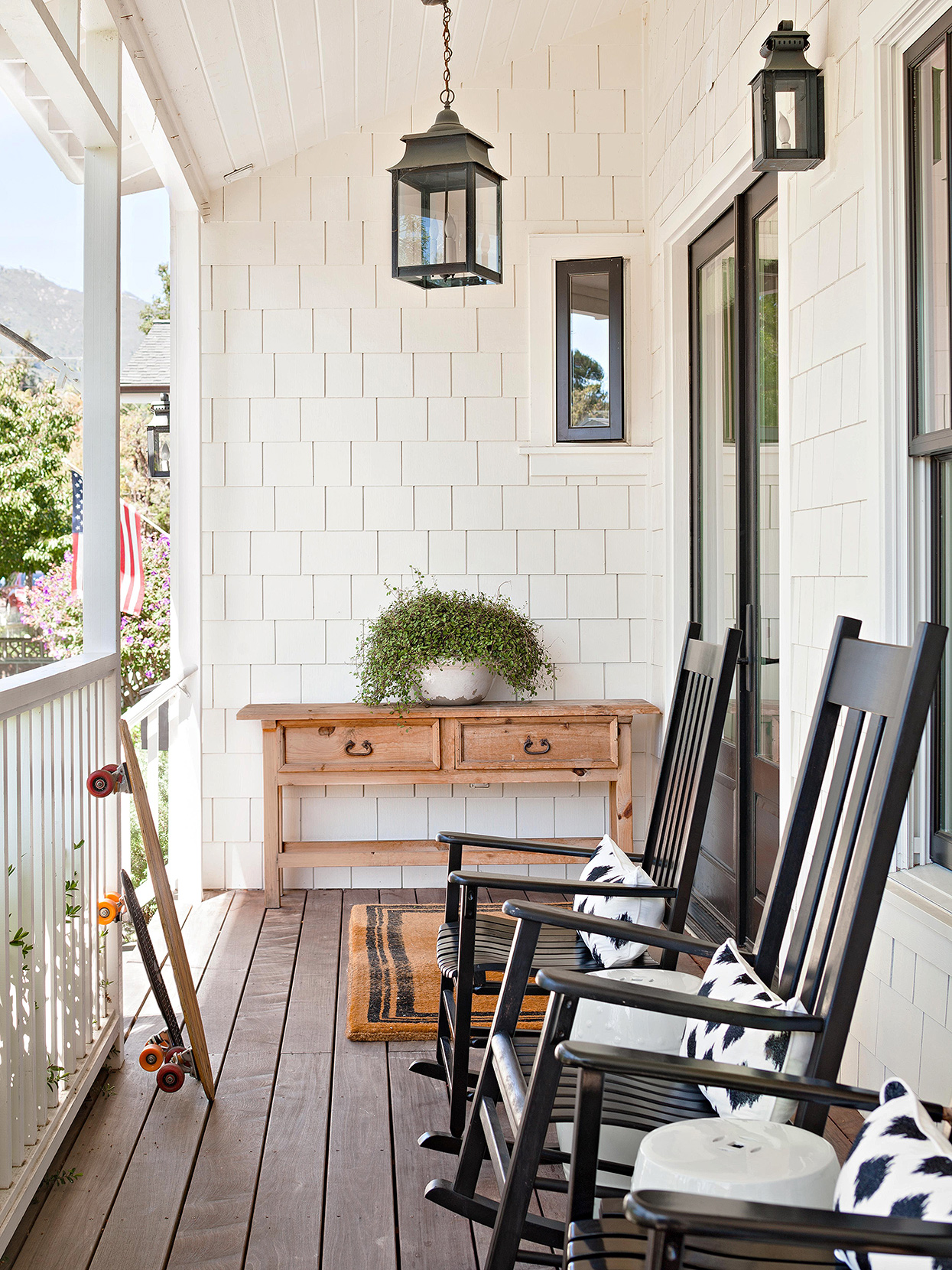 black rocking chairs on narrow farmhouse porch