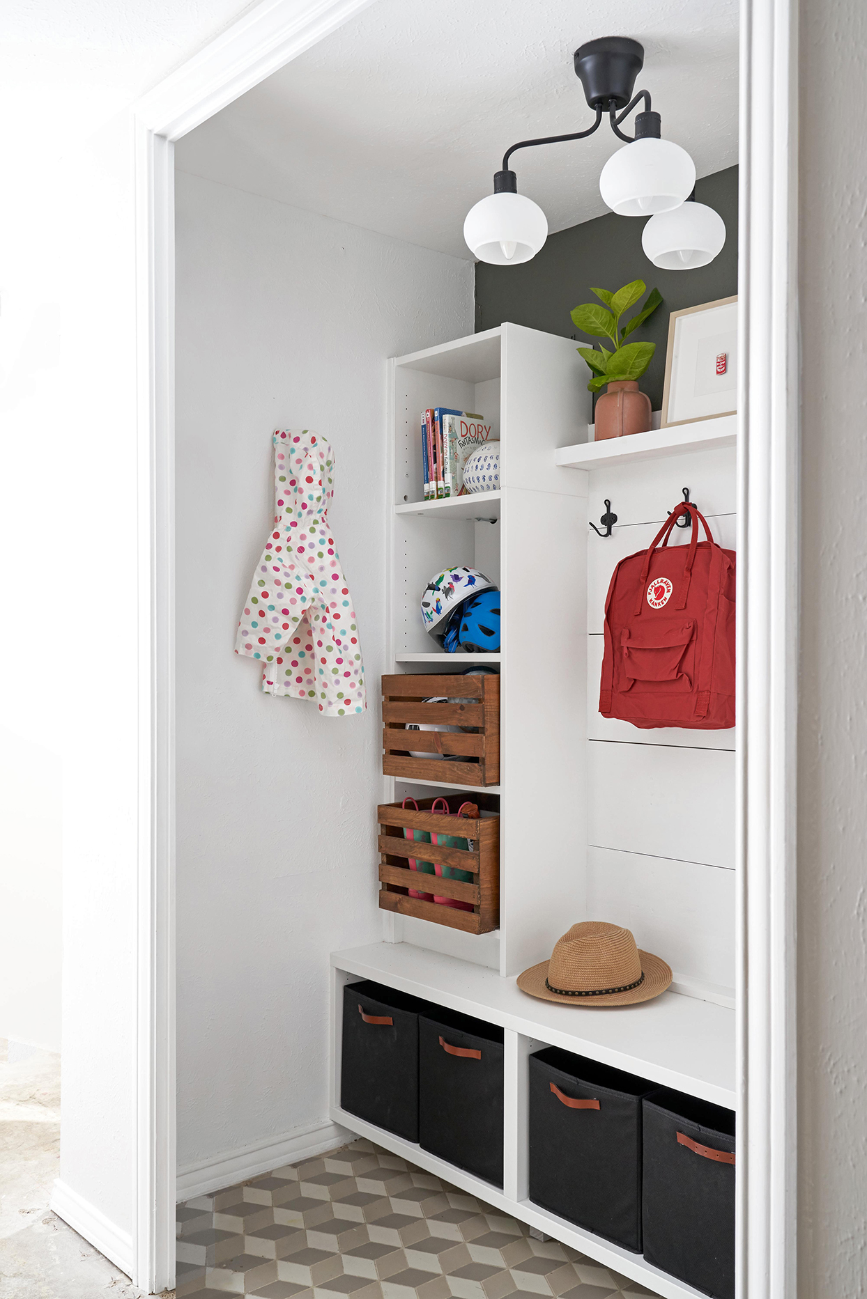 white and tan mudroom with wooden crates and black boxes