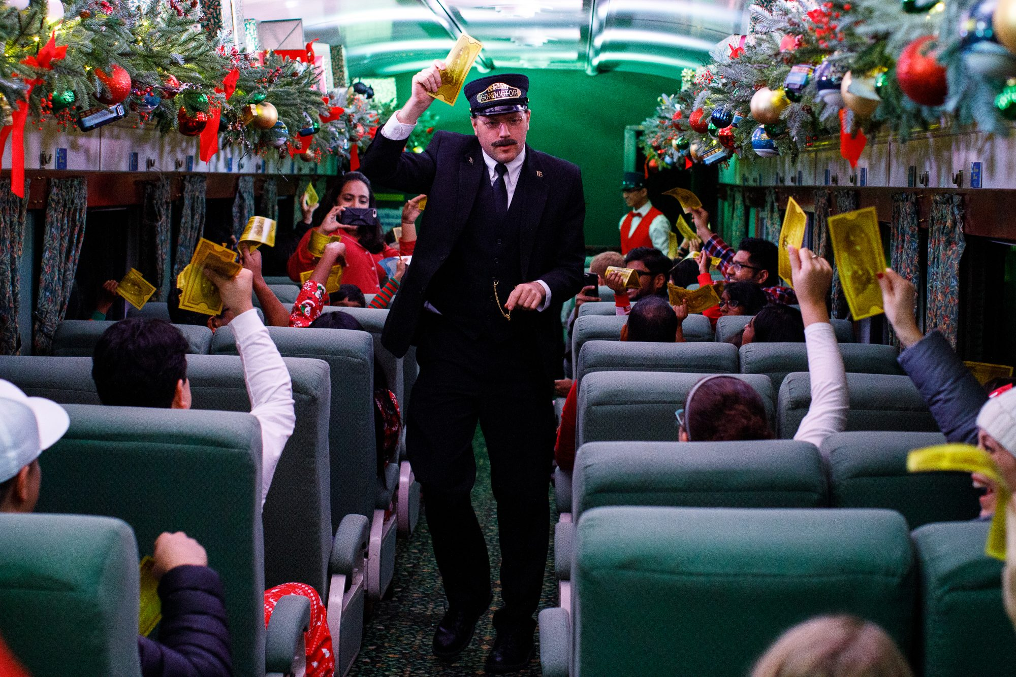 man dressed as train conductor on a train decorated for Christmas