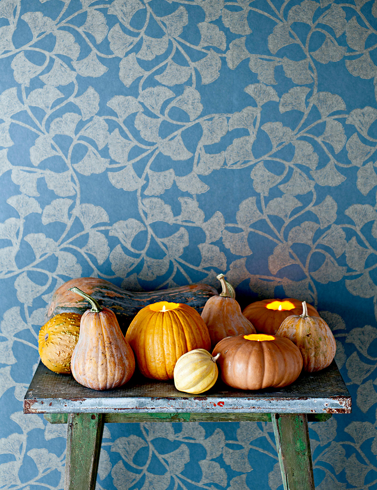 Pumpkins and gourds on table with candles inside
