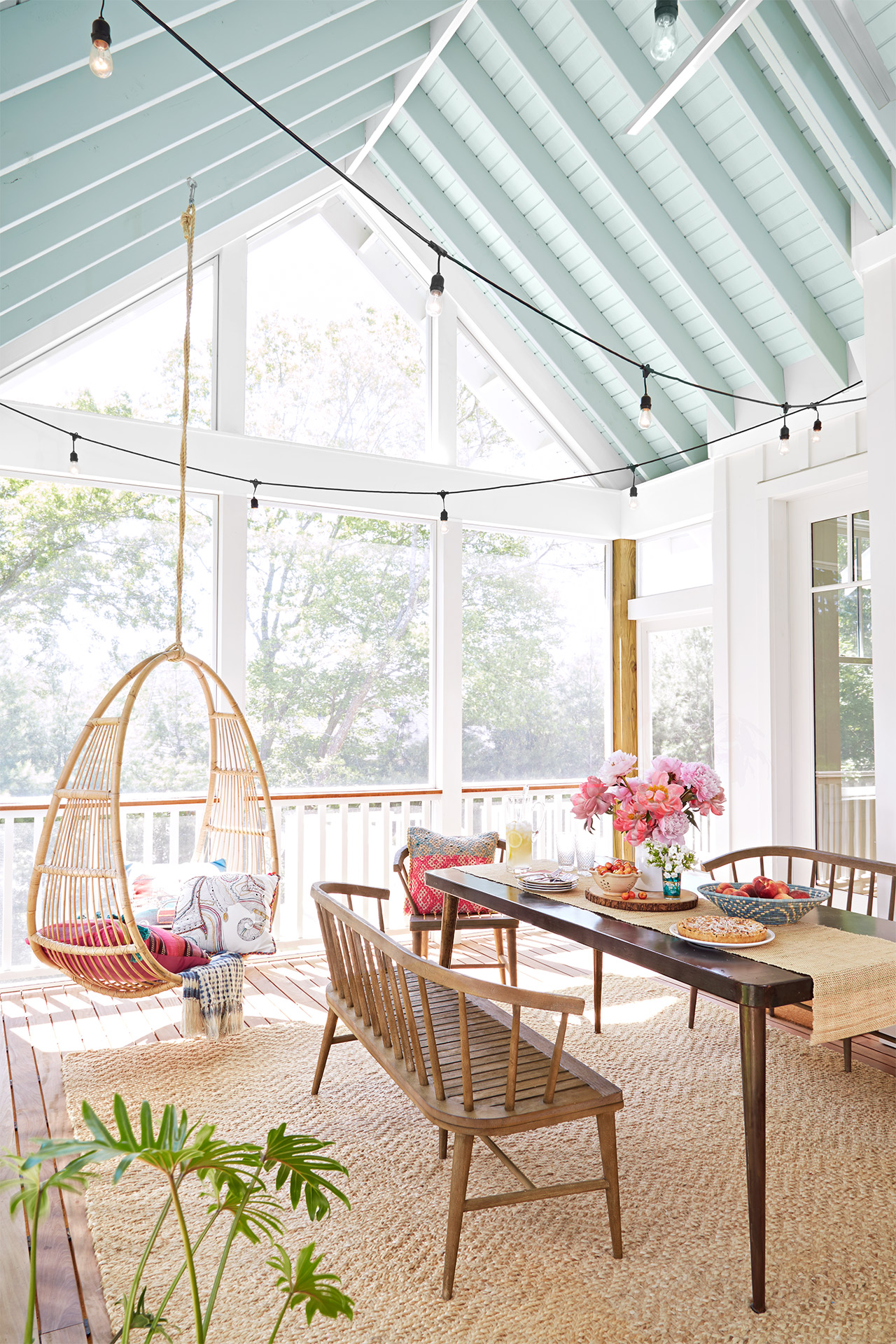 table with flowers by hanging chair on porch