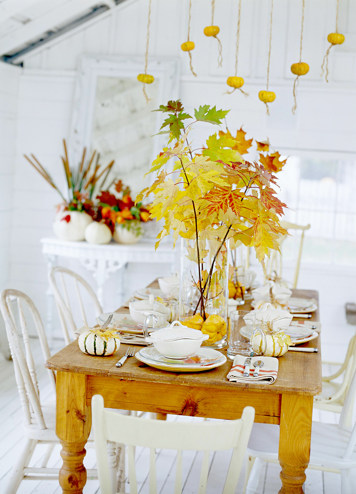 Table with leaf centerpiece and hanging small pumpkins