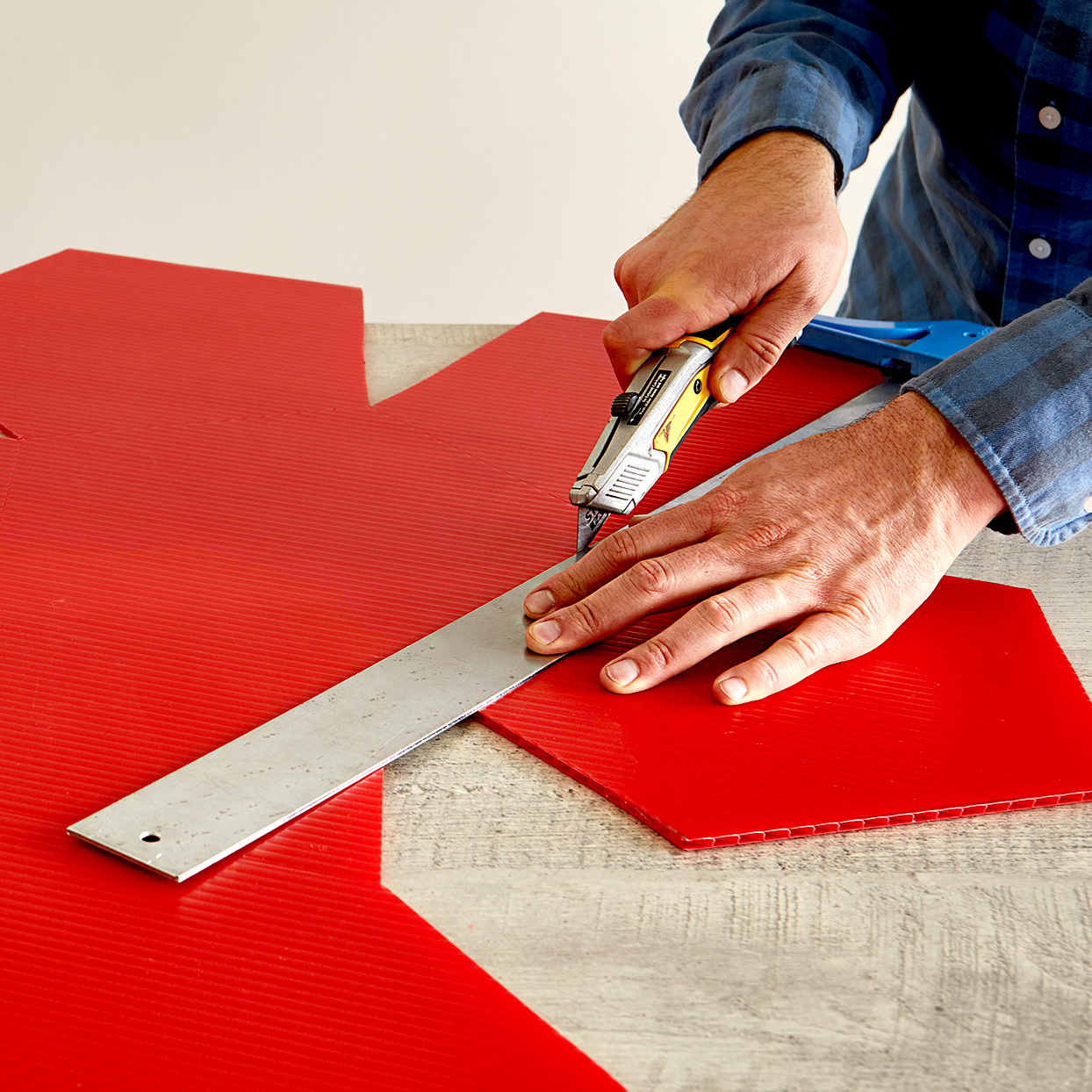 Person using box cutter on red pattern
