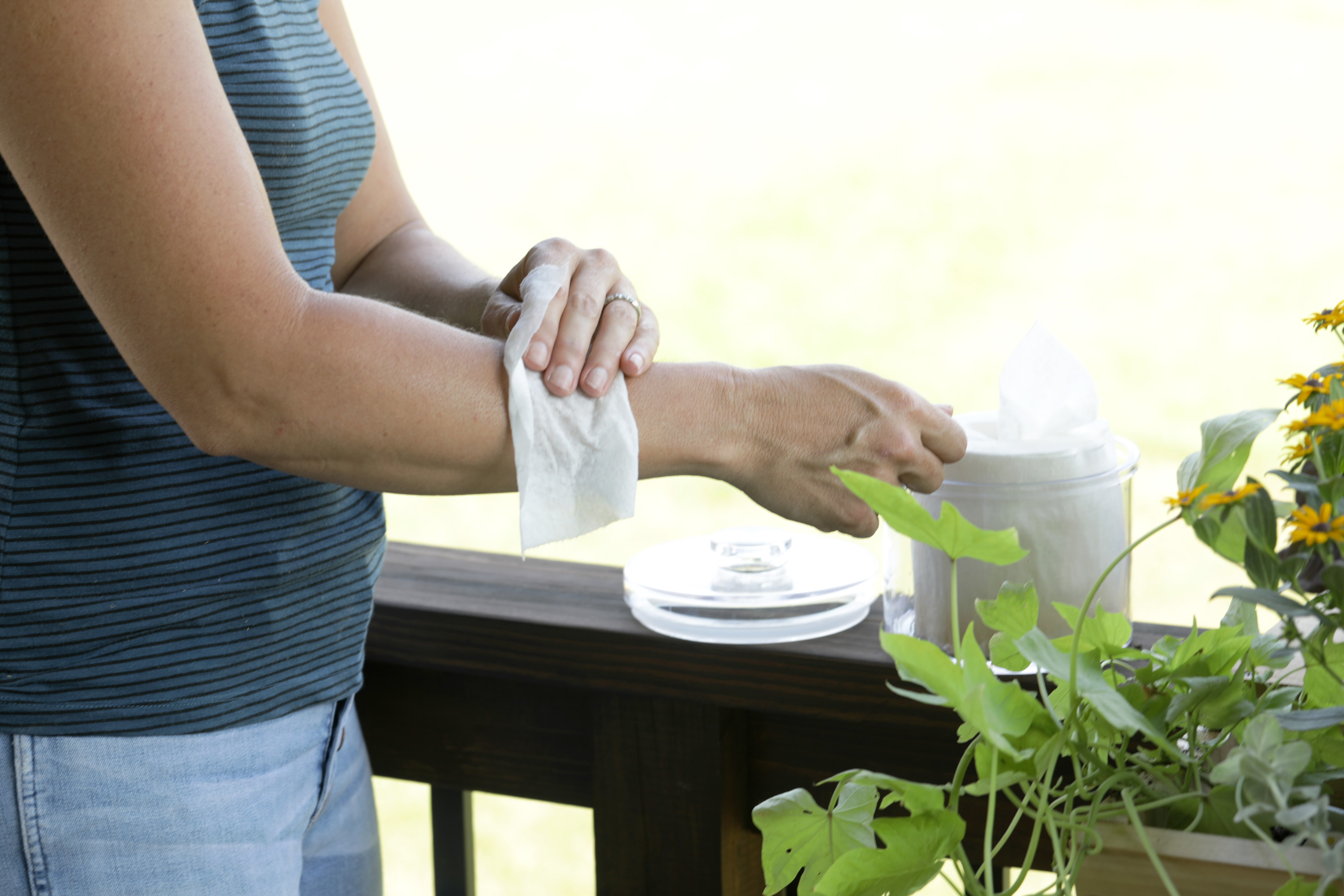 woman using mosquito wipe on arm