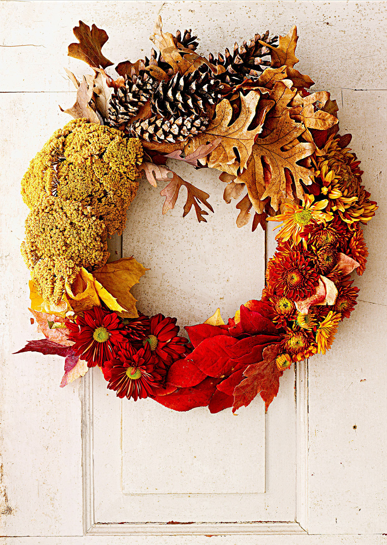 Fall wreath made of leaves, flowers, and pinecones
