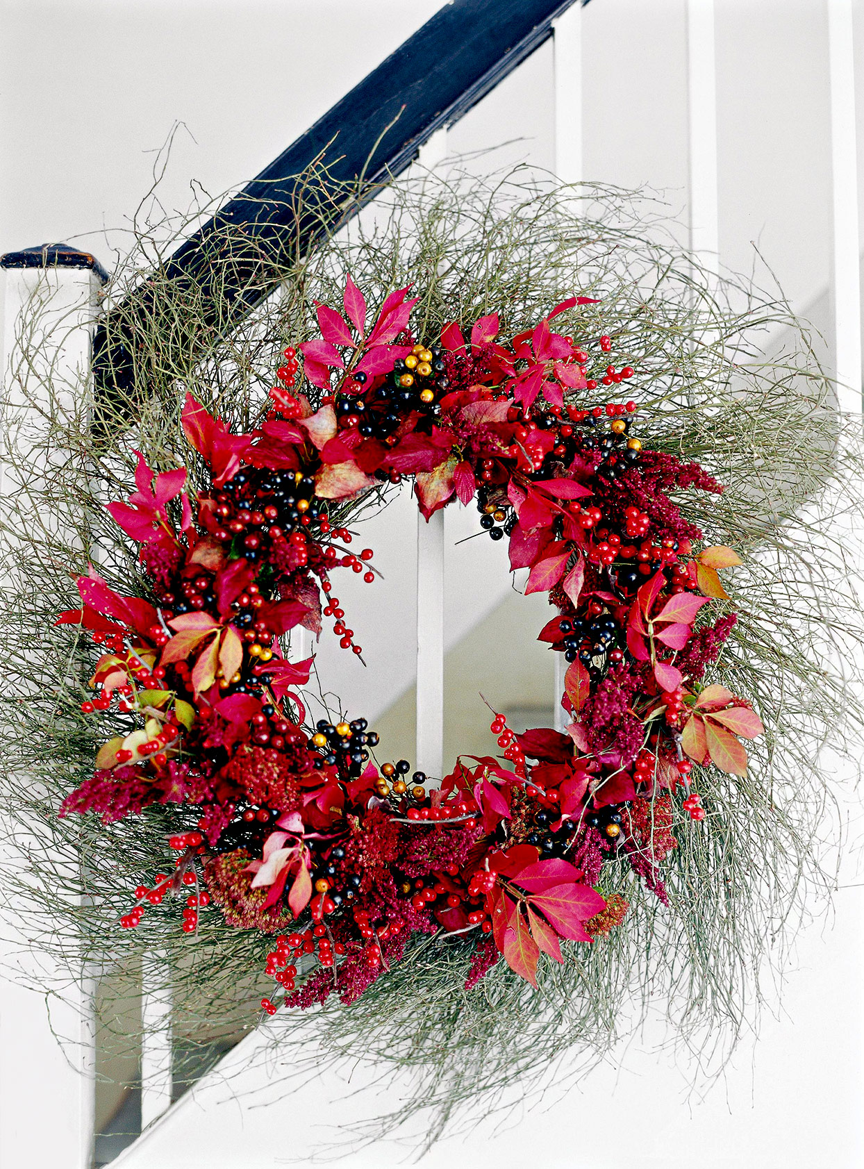 Wreath made of green plants and red berries and flowers