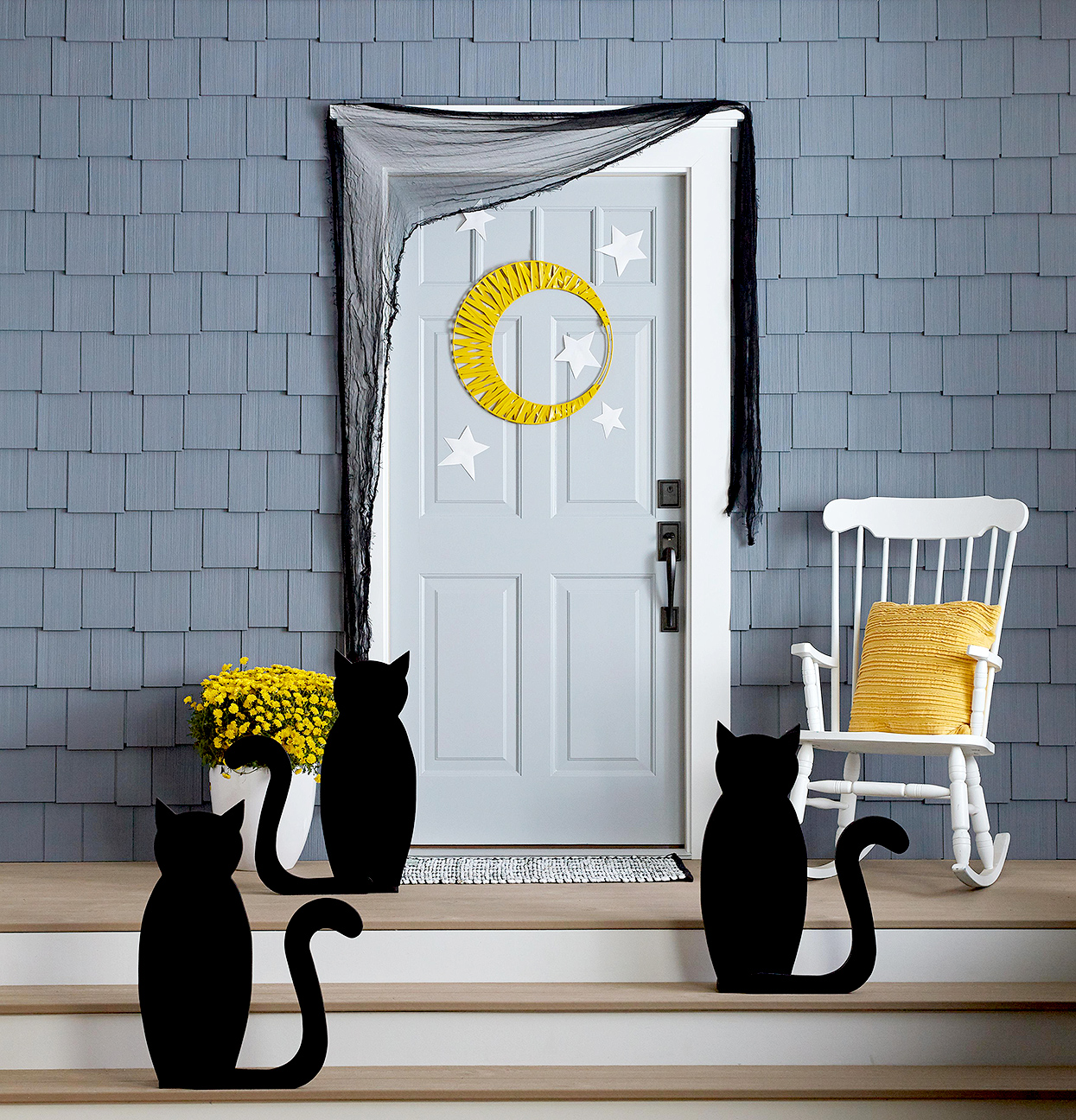 front door with cat cutouts and moon decor
