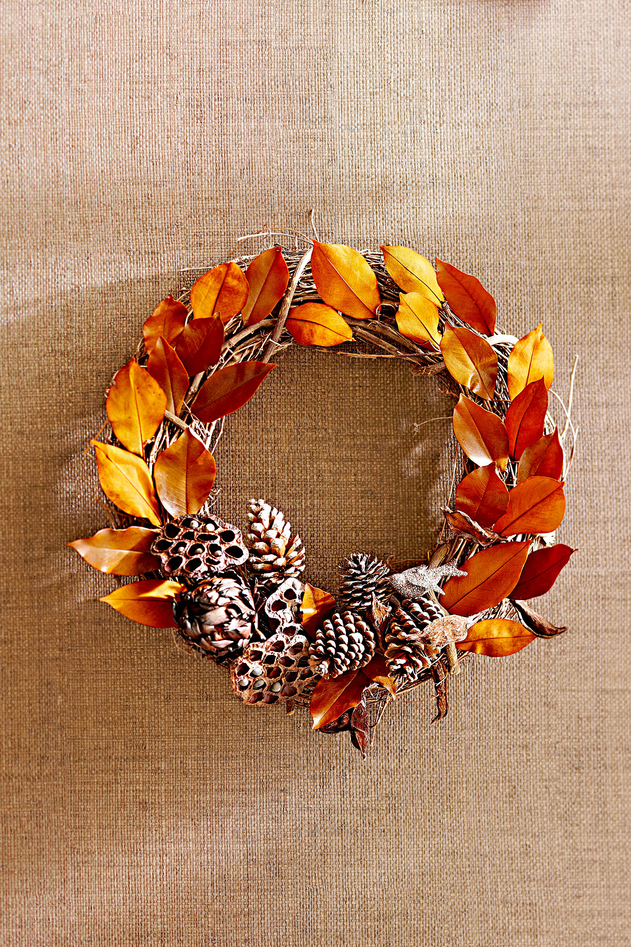 Wreath made of leaves, branches, seed pods, and pinecones