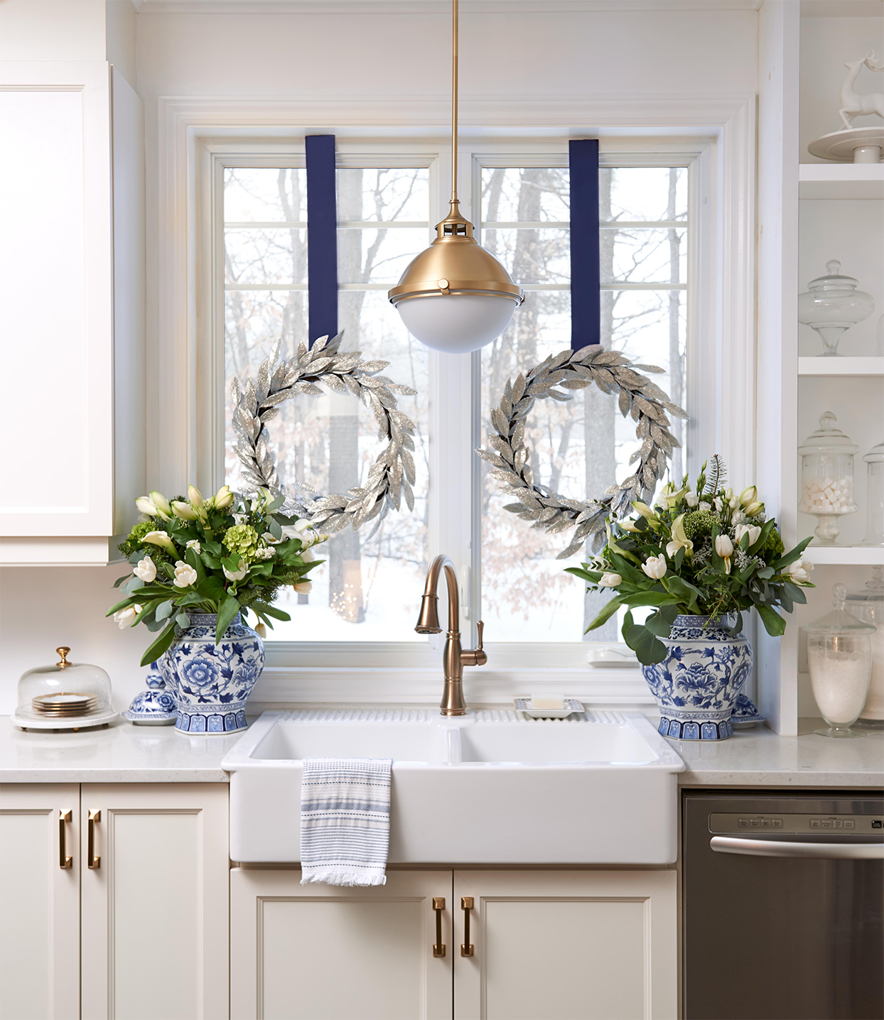 blue and silver wreaths hanging against window above white kitchen sink