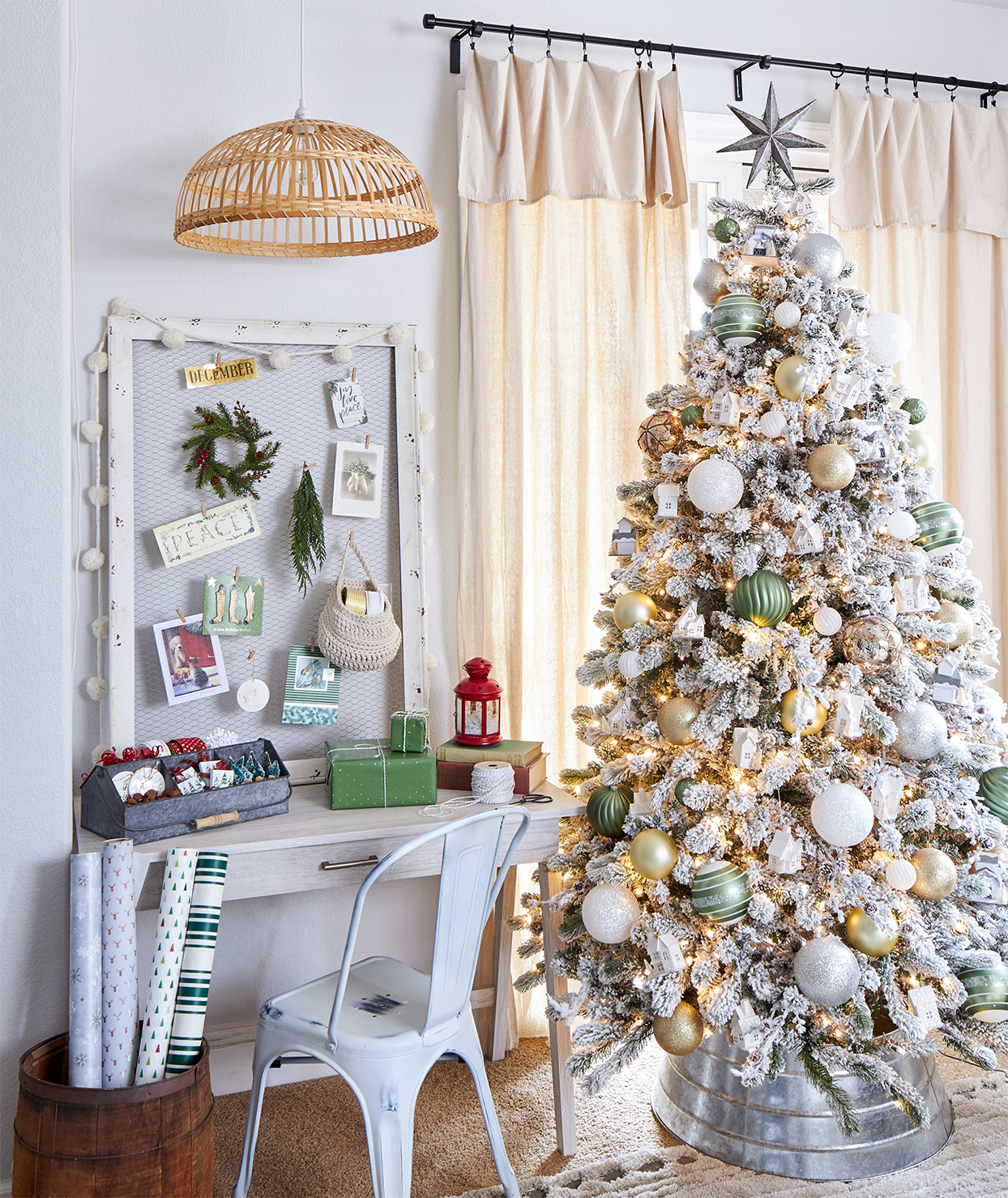 white christmas tree with green and metallic ornaments next to desk