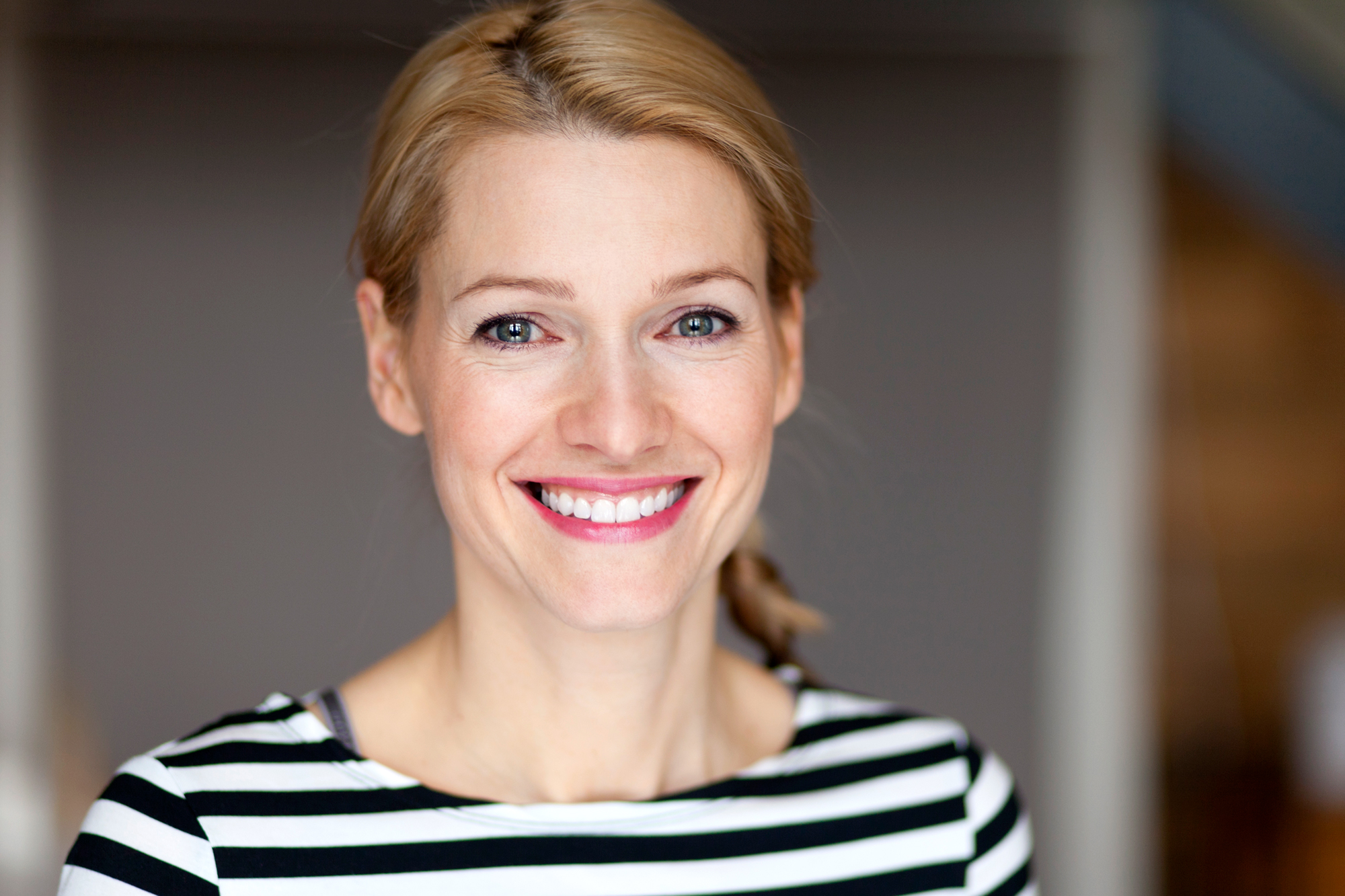 portrait of woman with blonde hair smiling and wearing a black and white striped shirt
