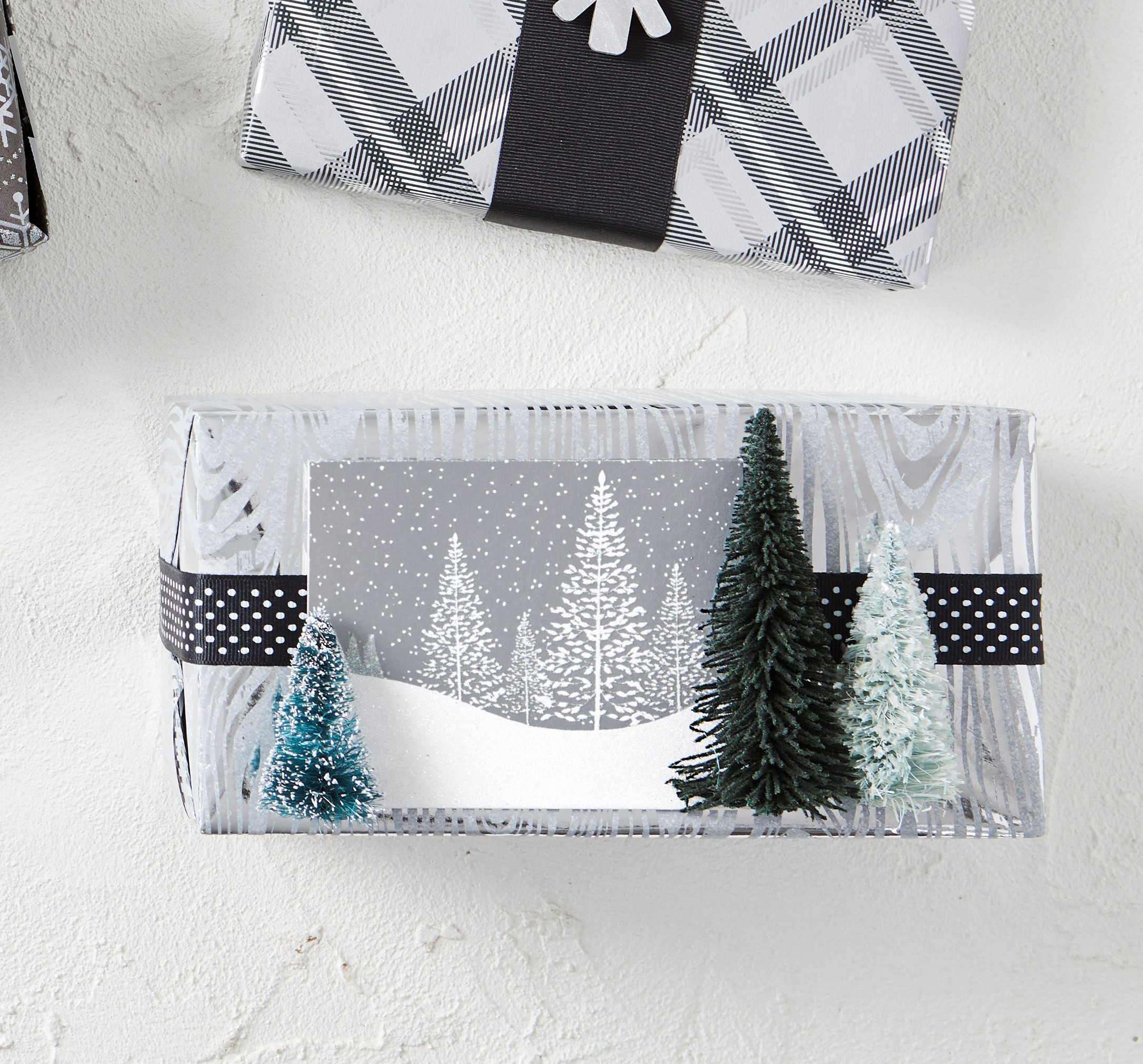 Create a mini holiday scene atop your wrapping paper. Choose materials that speak to the woodland theme: woodgrain paper, ribbon with dots of falling snow, a card that sets the background with snow and forest, and mini bottle-brush trees that pull the scene forward.Wrap your gift and add a band of ribbon down the center lengthwise. Trim the ends so they just meet, and use hot-glue to hold them in place at the center front. (Any overlap might create a bump under your card.) With double-stick tape, attach a holiday card, then hot-glue bottle-brush trees to the left and right of the card.