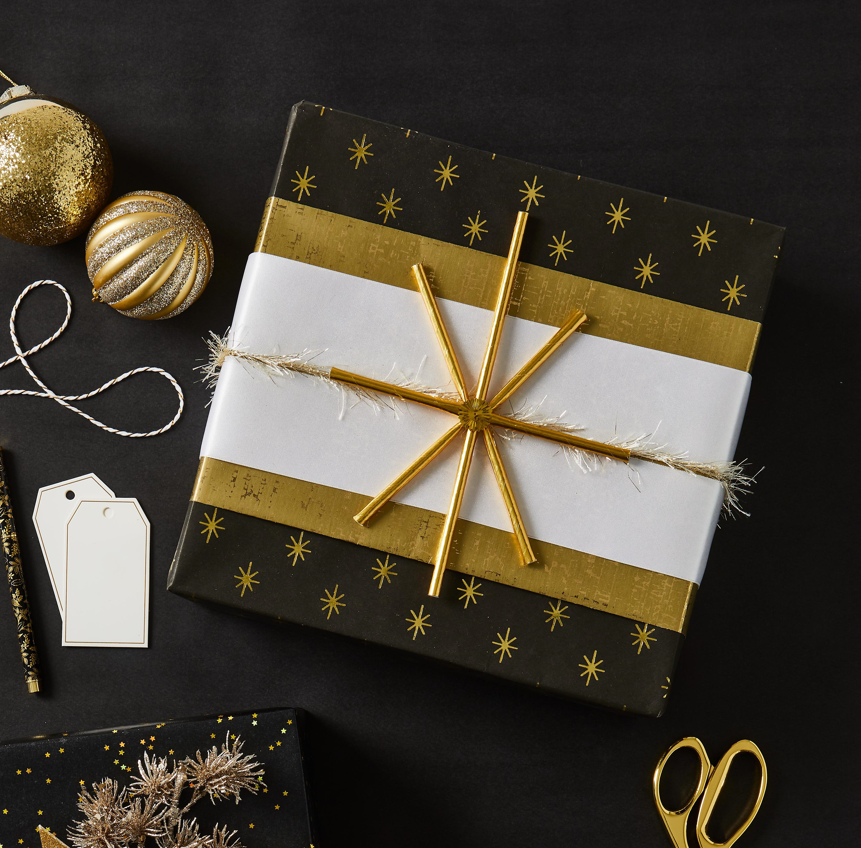 rectangle package wrapped in gold and white paper with white paper tags and gold sparkly ball ornaments next to it